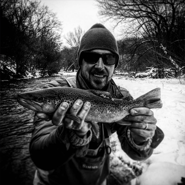 Black and white image of Aaron holding a trout